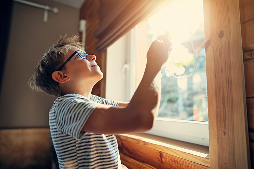 Little boy opening the roller blinds in the morning on sunny day.